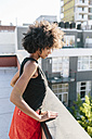 Young woman standing on rooftop in Brookliyn, looking down - GIOF02105