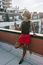 Relaxed woman sitting on rooftop in Brooklyn, using smart phone - GIOF02108