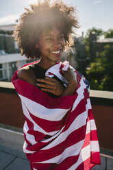 Young woman standing on rooftop warpped in US American flag - GIOF02117