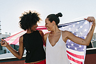 Female friends holding US American flag, standing on rooftop - GIOF02120