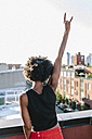 Happy young woman standing on rooftop in Brookly making victory sign - GIOF02123