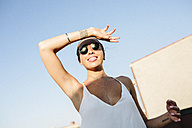 Young woman with sunglasses shielding eyes against sun - GIOF02126