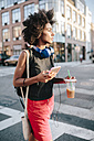 Young woman with headphones and smart phone crossong street in Brooklyn, carying take away drink - GIOF02129