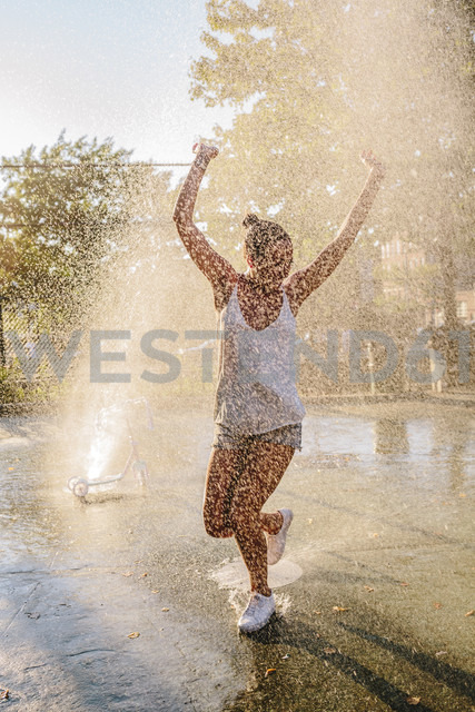 Young woman jumping water jet of a fountain - GIOF02132