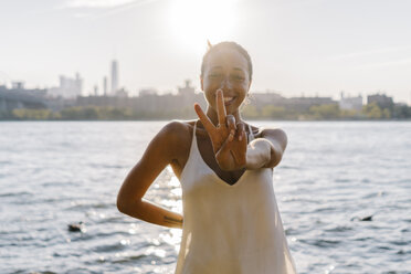 Young woman in Brooklyn standing at East River giving victory sign - GIOF02135