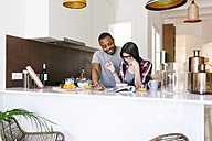 Young couple having breakfast in the kitchen and reading magazine - VABF01205