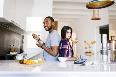 Young couple having breakfast in the kitchen, standing back to back - VABF01223