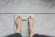 Woman standing on bathroom scales with sticky note of ideal weight - CHPF00371