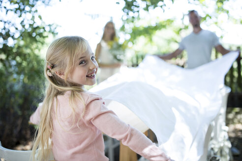 Smiling girl with her parents spreading out tablecloth in garden - WESTF22768