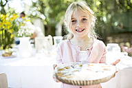 Portrait of smiling girl holding a pie outdoors - WESTF22771