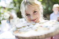 Portrait of smiling girl holding a pie outdoors - WESTF22774