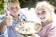 Portrait of smiling girl with brother holding a pie outdoors - WESTF22777