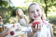 Portrait of smiling girl holding peach outdoors - WESTF22780
