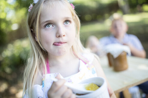 Girl eating jelly outdoors - WESTF22783