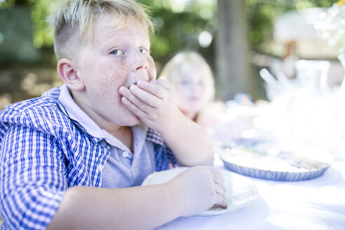 Portrait of boy eating at garden table - WESTF22789