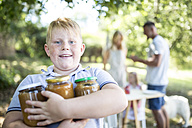 Portrait of boy holding jars outdoors with family in background - WESTF22804