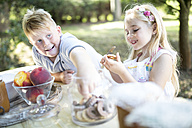 Sister and brother eating cakes at garden table - WESTF22807