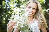 Smiling woman holding jug with flowers outdoors - WESTF22813