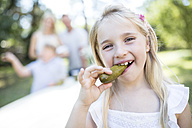 Portrait of girl eating gherkin outdoors with family in background - WESTF22816
