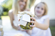 Mother and daughter holding jar with preserved gherkins outdoors - WESTF22822
