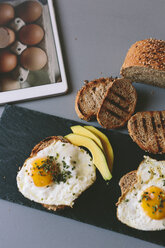 Breakfast with eggs, avovados and toasted bread on a table with digital tablet - GIOF02149