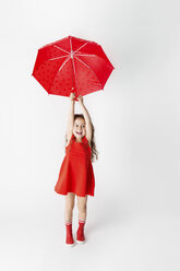 Smiling little girl in a red dress and red rain boots holding red umbrella in front of white background - LITF00500
