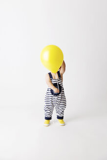 Toddler wearing striped dungarees and yellow rain boots hiding his face behind yellow balloon - LITF00506