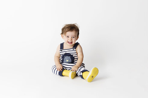 Laughing toddler wearing striped dungarees and yellow rain boots sitting in front of white background - LITF00509