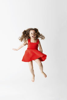 Laughing little girl in a red dress jumping in the air in front of white background - LITF00512