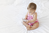 Baby girl sitting on white bed playing with smartphone - LITF00515