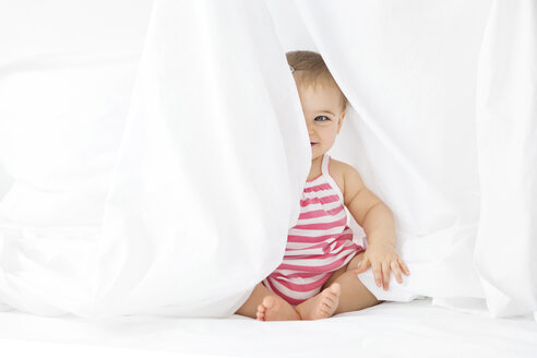 Smiling baby girl sitting on a white bed playing peek-a-boo behind bed sheet - LITF00521