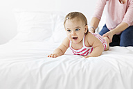 Portrait of smiling baby girl together with her mother on white bed - LITF00530