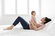 Mother and baby girl together on a bed - LITF00533