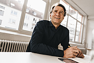 Smiling mature businessman at table in office - JOSF00671