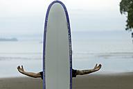 Man on the beach behind surfboard - KNTF00676