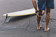 Surfer at the beach attaching surfboard leash - KNTF00679