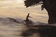 Indonesia, Java, man surfing at sunset - KNTF00694