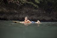 Indonesia, Java, man lying on surfboard on the sea - KNTF00697