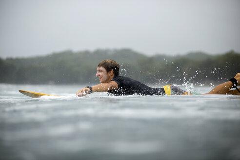 Indonesia, Java, man lying on surfboard on the sea - KNTF00718