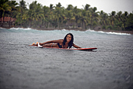 Indonesia, Java, woman lying on surfboard on the sea in rain - KNTF00721