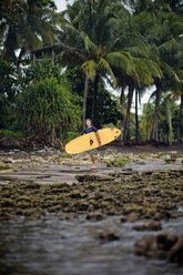 Indonesia, Java, man carrying surfboard at the coast - KNTF00724