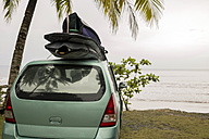 Indonesia, Java, car with surfboards on the roof at the coast - KNTF00727