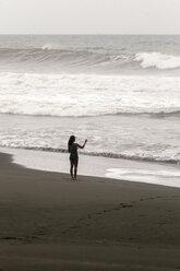 Indonesia, Java, woman at ocean coastline - KNTF00730