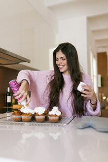 Young woman topping cup cakes with whipped cream - VABF01236