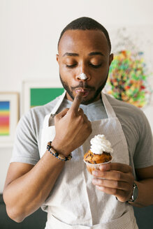 Young man eating a cup cake with whipped cream, licking finger - VABF01239
