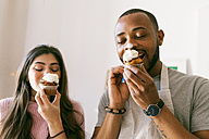 Young couple having fun, eating fresh cupcakes - VABF01242
