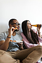 Young couple at home eating pizza and drinking beer - VABF01251