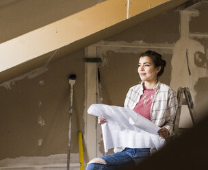 Young woman renovating her new home, holding construction plan - UUF10074