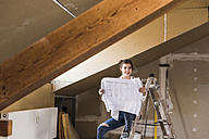 Young woman renovating her new home, holding construction plan - UUF10077