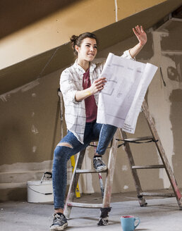 Young woman renovating her new home, holding construction plan - UUF10080